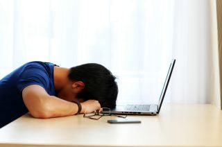 Asian man sleeping on the table with laptop at home