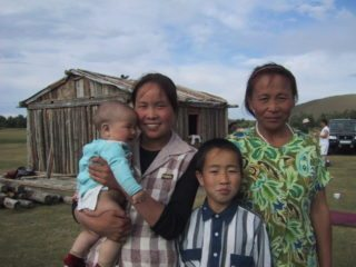 A pastor's family outside their home in the countryside. This is typical outside the cities.
